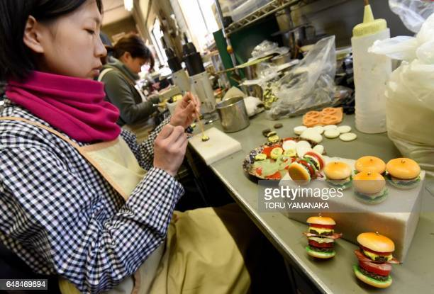 This picture taken on January 18 2017 shows a craftswoman of Fake Food Hatanaka making plastic hamburger earrings at the company's studio in...