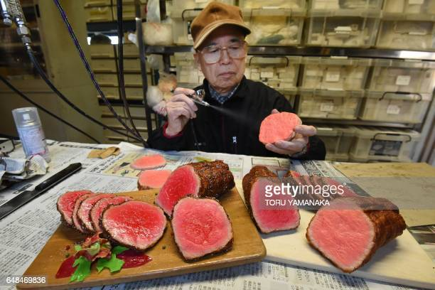 This picture taken on January 18 2017 shows Noriyuki Mishima a craftsman at Fake Food Hatanaka spraying paint on a plastic food replica that...