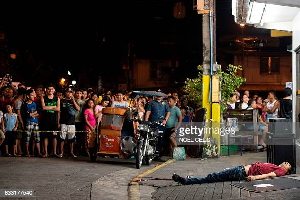 TOPSHOT This picture taken on January 18 shows a body of an alleged drug user on the ground after an unidentified gunmen shot him dead in Manila...