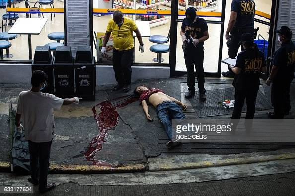 This picture taken on January 18 shows a body of an alleged drug user on the ground after an unidentified gunmen shot him dead in Manila Philippine...