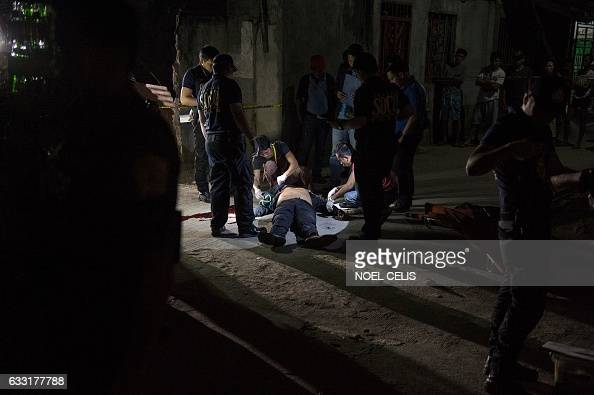 This picture taken on January 18 shows policemen investigating a body of an alleged drug user on the ground after an unidentified gunmen shot him...