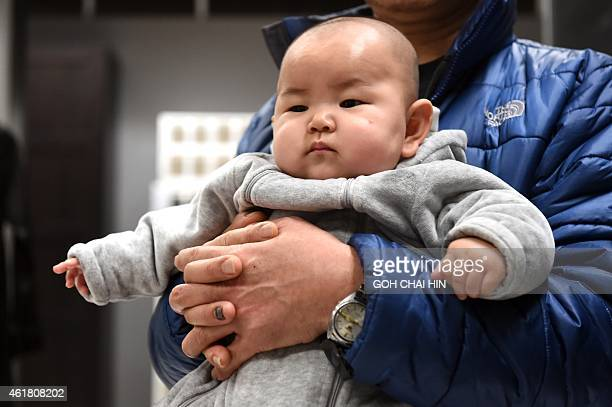 This picture taken on January 19 2015 shows a Chinese baby in the arms of his father at a furniture store in Beijing China's workingage population...