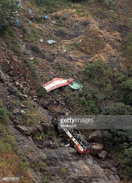 This picture taken on January 2 2014 shows the remains of the local bus that slid off a mountain road killing at least 27 people at Malshej Ghat in...