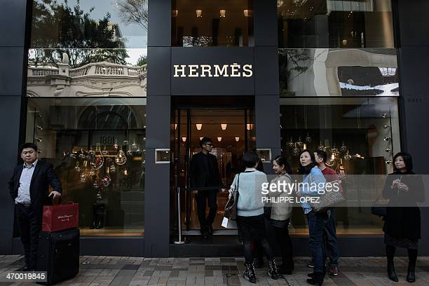 This picture taken on January 20 2014 shows tourists queuing in front of a luxury shop in a popular shopping district in Hong Kong Hong Kong chief...