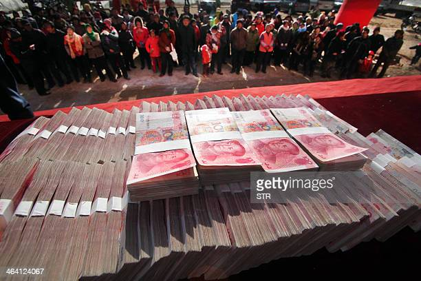 This picture taken on January 20 2014 shows villagers gathering to receive their share of one million yuan paid out in yearend bonuses by a tea...