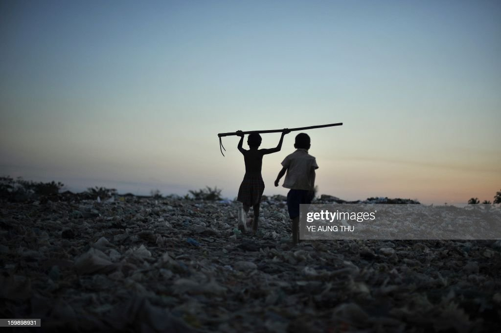 This picture taken on January 22, 2013 shows Myanmar boys holding a tool used to collect material for sale and recycling as they leave a waste dump on the outskirts of Yangon. Myanmar is one of the poorest countries in Asia after decades of economic mismanagement and isolation under army rule, but could become Asia's next economic engine if it enacts vast reforms, the IMF said in November of 2012. AFP PHOTO / Ye Aung THU