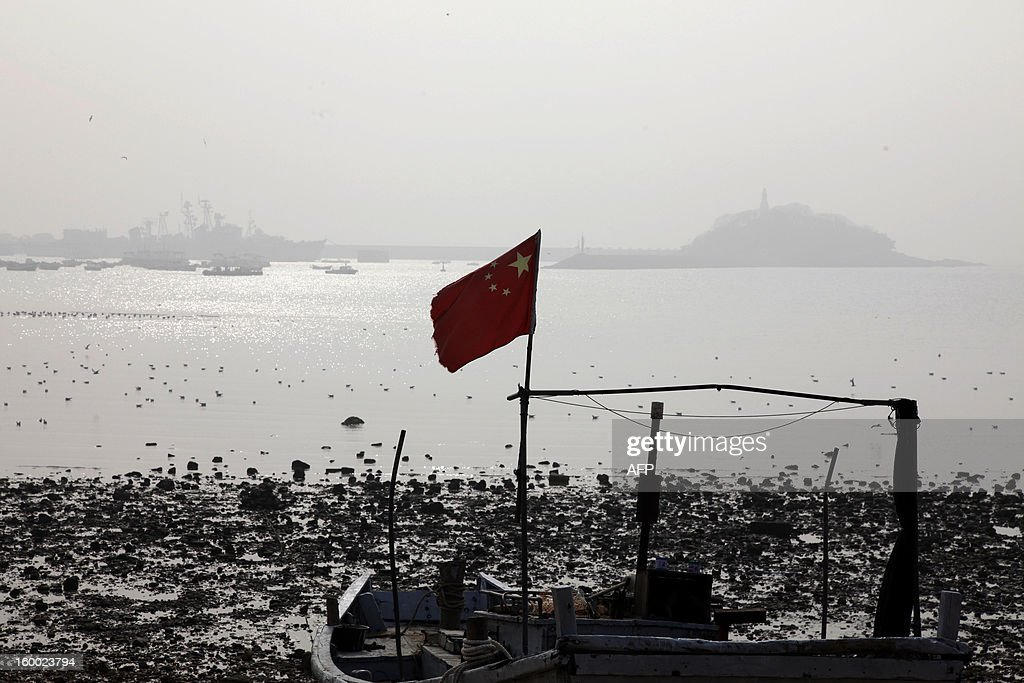 This picture taken on January 24, 2013 shows a Chinese national falg flying in the heavy smog in Qingdao, east China's Shandong province. China has cleaned up its air before but experts say that if it wants to avoid the kind of smog that choked the country earlier, it must overhaul an economy fuelled by heavily polluting coal and car use. CHINA OUT AFP PHOTO
