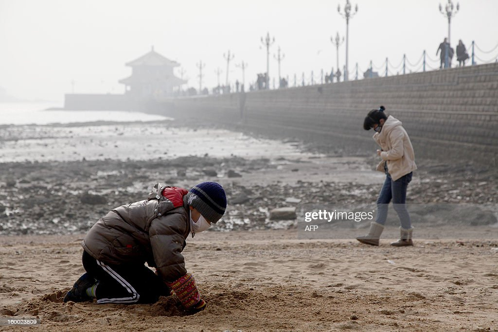 This picture taken on January 24, 2013 shows a kid wearing a mask while playing in the heavy smog in Qingdao in east China's Shandong province. China has cleaned up its air before but experts say that if it wants to avoid the kind of smog that choked the country earlier, it must overhaul an economy fuelled by heavily polluting coal and car use. CHINA