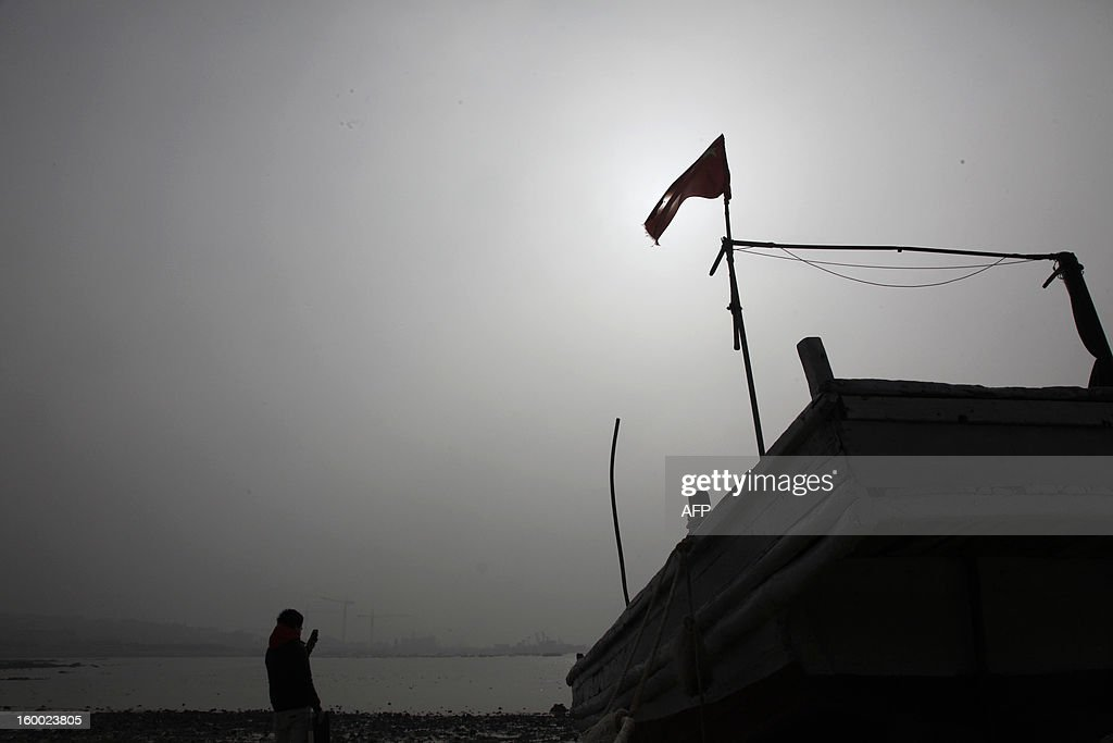 This picture taken on January 24, 2013 shows a man taking picture in the heavy smog in Qingdao in east China's Shandong province. China has cleaned up its air before but experts say that if it wants to avoid the kind of smog that choked the country earlier, it must overhaul an economy fuelled by heavily polluting coal and car use. CHINA