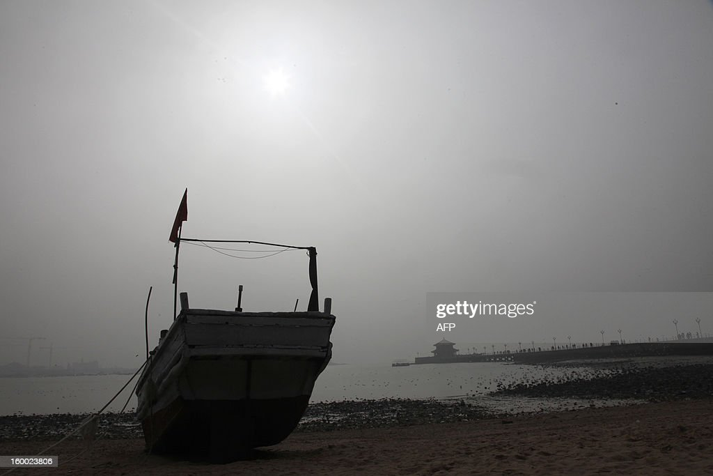 This picture taken on January 24, 2013 shows heavy smog hanging in Qingdao in east China's Shandong province. China has cleaned up its air before but experts say that if it wants to avoid the kind of smog that choked the country earlier, it must overhaul an economy fuelled by heavily polluting coal and car use. CHINA OUT AFP PHOTO