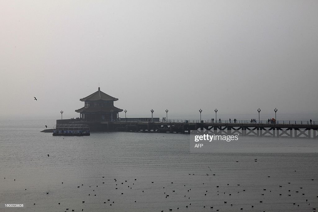 This picture taken on January 24, 2013 shows heavy smog hanging in Qingdao in east China's Shandong province. China has cleaned up its air before but experts say that if it wants to avoid the kind of smog that choked the country earlier, it must overhaul an economy fuelled by heavily polluting coal and car use. CHINA