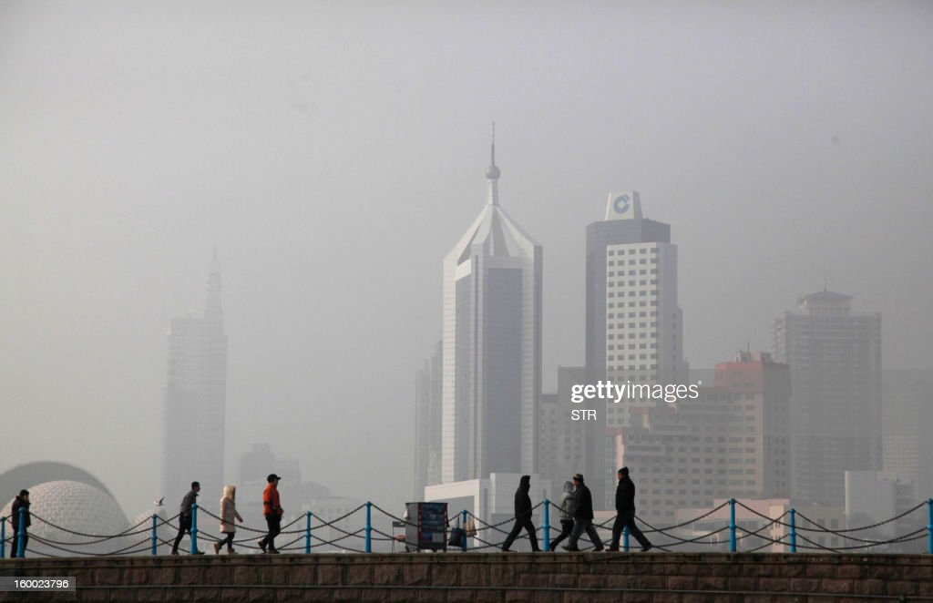 This picture taken on January 24, 2013 shows people walking in the heavy smog in Qingdao, east China's Shandong province. China has cleaned up its air before but experts say that if it wants to avoid the kind of smog that choked the country earlier, it must overhaul an economy fuelled by heavily polluting coal and car use. CHINA