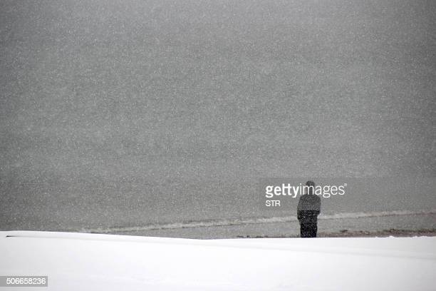 This picture taken on January 24 2016 shows a man standing in snow along the beach in Rongcheng in eastern China's Shandong province Snow sleet and...