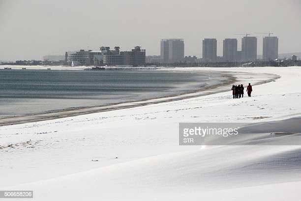 TOPSHOT This picture taken on January 24 2016 shows people walking along the snowcovered beach in Rongcheng in eastern China's Shandong province Snow...