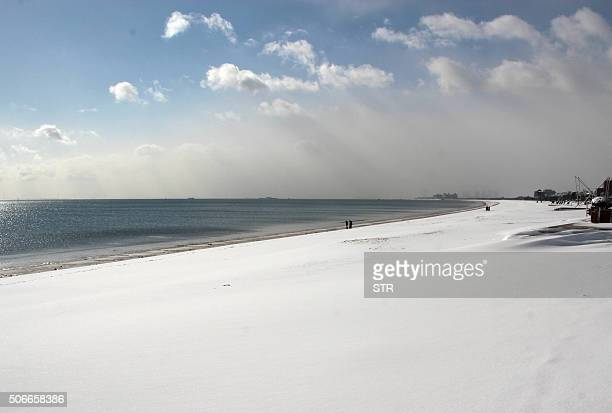 This picture taken on January 24 2016 shows people walking along the snowcovered beach in Rongcheng in eastern China's Shandong province Snow sleet...