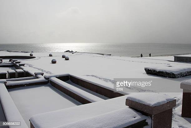 This picture taken on January 24 2016 shows the snowcovered coast in the city of Rongcheng in eastern China's Shandong province Snow sleet and icy...