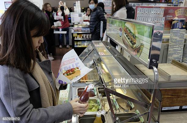 This picture taken on January 24 2017 shows a customer holding a hotdog at a 7Eleven convenience store in Taipei Borrow library books buy train...