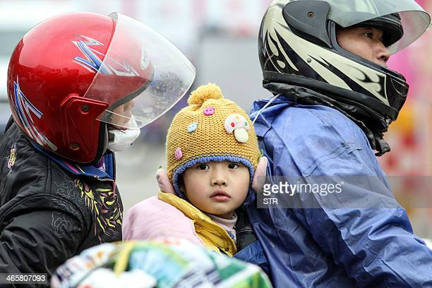 This picture taken on January 25 2014 shows a Chinese family arriving on a motorcycle at a pitstop in Wuzhou Guangxi province as they join thousands...