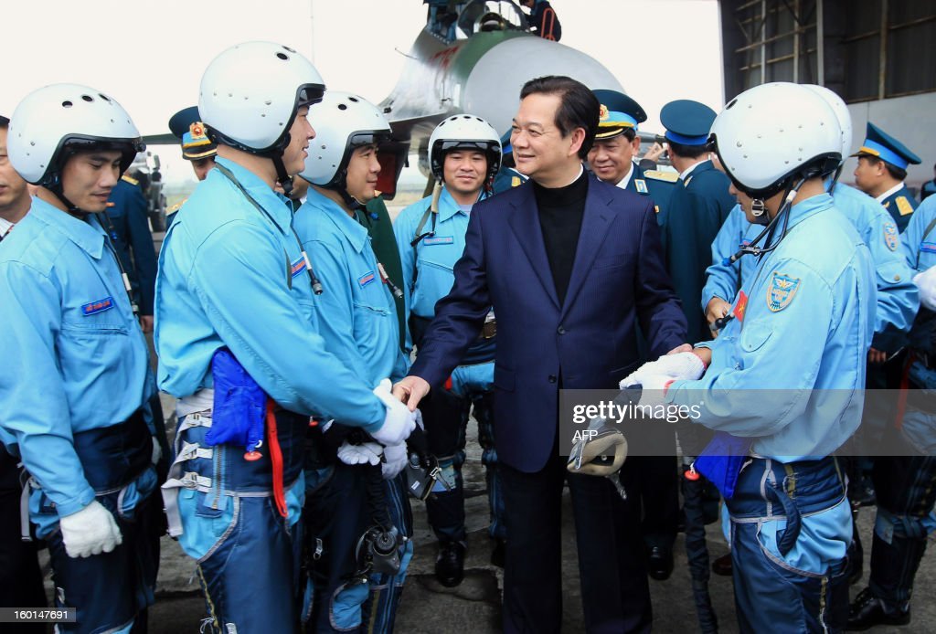 This picture taken on January 26, 2013 by the Vietnam News Agency shows Vietnamese Prime Minister Nguyen Tan Dung (C) chatting to pilots as he visits a Vietnamese Air Force regiment based in the north-central province of Thanh Hoa. Amid rising maritime tension and island disputes in South China Sea, mostly with its northern Chinese neighbour, Vietnam's official media reported in recent months that Hanoi had ordered mainly from Russia modern weapons including submarines, missiles and jets to strengthen the Southeast Asian communist nation. AFP PHOTO/Vietnam News Agency