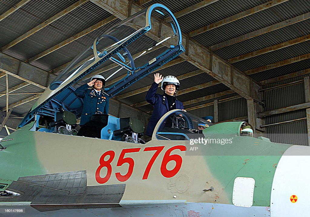 This picture taken on January 26, 2013 by the Vietnam News Agency shows Vietnamese Prime Minister Nguyen Tan Dung (R) waving from a Russian-made Sukhoi 30 MK2 jet as he visits a Vietnamese Air Force regiment based in the north-central province of Thanh Hoa. Amid rising maritime tension and island disputes in South China Sea, mostly with its northern Chinese neighbour, Vietnam's official media reported in recent months that Hanoi had ordered mainly from Russia modern weapons including submarines, missiles and jets to strengthen the Southeast Asian communist nation. AFP PHOTO/Vietnam News Agency