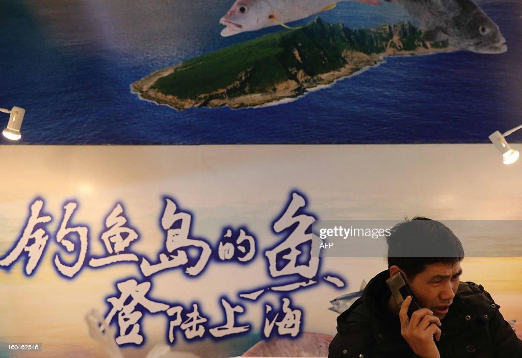 This picture taken on January 26, 2013 shows a fishmonger making a phone call in front of a 'Diaoyu Island fish' advertisement in a market in Shanghai. All of the fish were caught in waters near the disputed islands, known as Diaoyu in China and Senkaku in Japan. Japan is embroiled in a row with China over the chain of islands in the East China Sea. CHINA OUT AFP PHOTO
