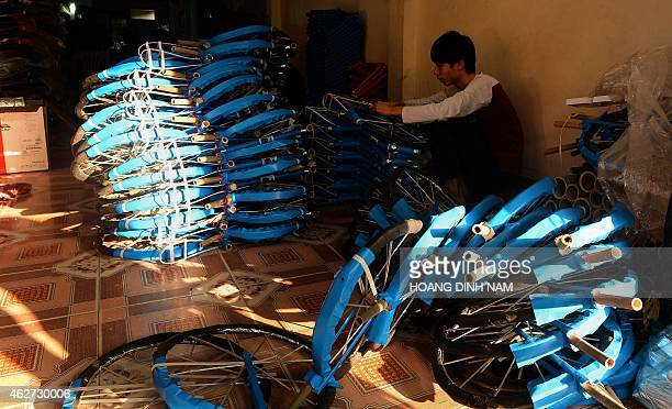 This picture taken on January 26 2015 shows a man making votive paper bicycles for the coming 'Tet' lunar New Year holidays in the village of Dong Ho...