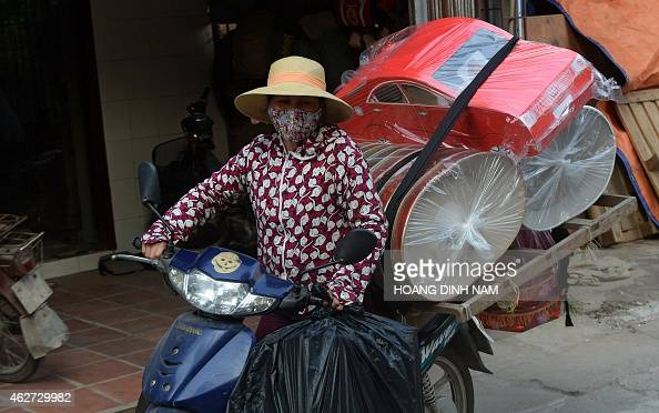 This picture taken on January 26 2015 shows a woman transporting votive paper items on her motorbike ahead of the coming 'Tet' lunar New Year...