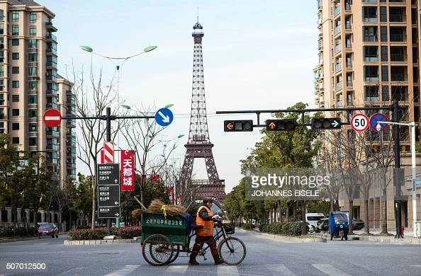 TOPSHOT This picture taken on January 26 2016 shows a street clearn crossing the street in front of a replica of the Eiffel Tower in Tianducheng a...