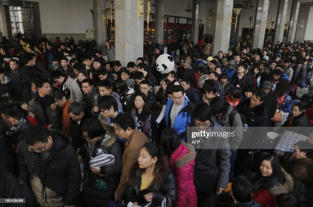 This picture taken on January 26, 2013, the first day of Spring Festival travel season, shows a lady wearing a panda constume (C) queuing up in the waiting room to get on her train back to Cangzhou in Hefei from Beijing. The lady, together with other three female friends, said she would like to feel the special atmosphere of the Spring Festival travelling in this way. CHINA