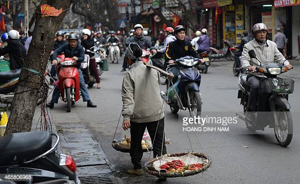 This picture taken on January 27 2014 shows a fruit vendor walking among motorcyclists in downtown Hanoi Known locally as Tet the lunar new year is...