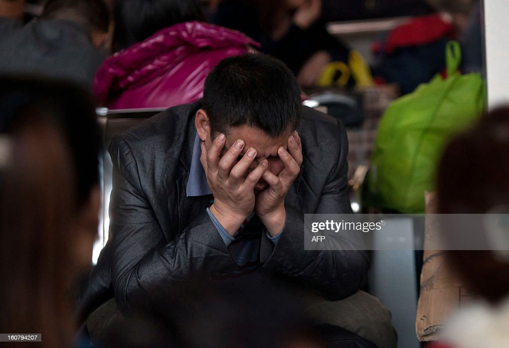 This picture taken on January 28, 2013 shows a man sitting in the square at Guangzhou train station waiting for his train back home for Lunar New Year, or Spring Festival. Passengers will log 220 million train rides during the 40-day travel season as they criss-cross the country to celebrate with their families, but just as making the trip home can be laborious -- often lasting one or two days -- so can simply acquiring a seat on the train, and every year complaints arise about the inefficiency or unfairness of the system, although an initiative allowing travelers to purchase tickets online aims to curb long queuing times. CHINA