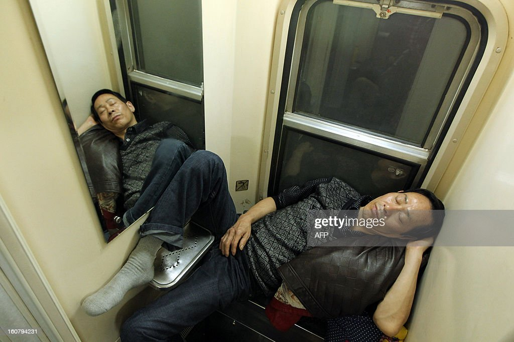 This picture taken on January 28, 2013 shows a man sleeping in the toilet of a train from Guangzhou to Changchun as people head back to their hometowns for the Lunar New Year, or Spring Festival. Passengers will log 220 million train rides during the 40-day travel season as they criss-cross the country to celebrate with their families, but just as making the trip home can be laborious -- often lasting one or two days -- so can simply acquiring a seat on the train, and every year complaints arise about the inefficiency or unfairness of the system, although an initiative allowing travelers to purchase tickets online aims to curb long queuing times. CHINA