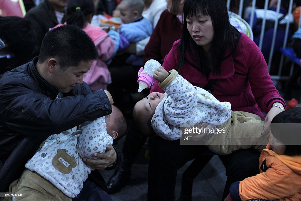 This picture taken on January 28, 2013 shows a pair of parents taking care of their two children in the square at Guangzhou train station waiting for their train back home for the Lunar New Year, or Spring Festival. Passengers will log 220 million train rides during the 40-day travel season as they criss-cross the country to celebrate with their families, but just as making the trip home can be laborious -- often lasting one or two days -- so can simply acquiring a seat on the train, and every year complaints arise about the inefficiency or unfairness of the system, although an initiative allowing travelers to purchase tickets online aims to curb long queuing times. CHINA OUT AFP PHOTO / BAI SHI