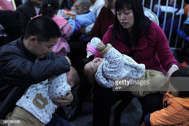 This picture taken on January 28 2013 shows a pair of parents taking care of their two children in the square at Guangzhou train station waiting for...