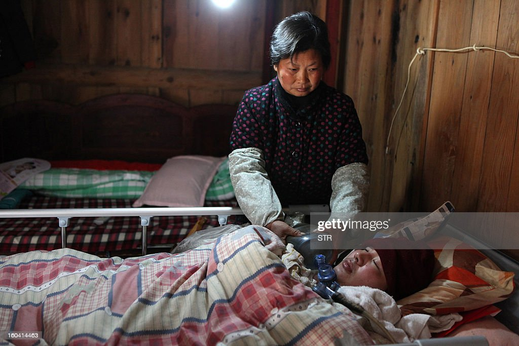 This picture taken on January 28, 2013 shows a self-made ventilator that Fu Xuepeng (not pictured), a former mechanic who was paralyzed in a road accident when he was 23 years old, uses to relieve his mother Wang Lanqin and father Fu Minzu (both not pictured) from having to use a hand pump to help him breathe, placed on the ground at his home in Taizhou, east China's Zhejiang province. According to state media, a local hospital has decided to help Fu's parents after reports that they have kept their son alive for more than five years using a hand pumped PVC resuscitator bag and a ventilator made by a local DIY expert. They took turns compressing their son's bag 24-hours a day, seven days a week, until they had someone making them a medical ventilator with a motor, a speed controller, a pushing bar and an air bag, which cost 200 yuan (32 USD). But to minimize the electricity bill, which adds up to 5 to 6 yuan a day if the machine is left running all day, the couple still compresses the bag by hand during the day and turns on the machine only at night. CHINA