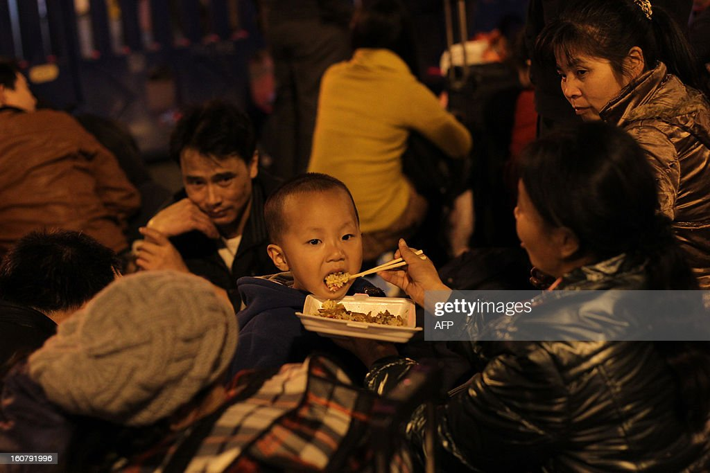 This picture taken on January 28, 2013 shows a woman feeding a little boy eating on the square of Guangzhou Train Station, waiting for their train back home for the Spring Festival. Passengers will log 220 million train rides during the 40-day travel season as they criss-cross the country to celebrate with their families, but just as making the trip home can be laborious -- often lasting one or two days -- so can simply acquiring a seat on the train, and every year complaints arise about the inefficiency or unfairness of the system, although an initiative allowing travelers to purchase tickets online aims to curb long queuing times. CHINA OUT AFP PHOTO / BAI SHI