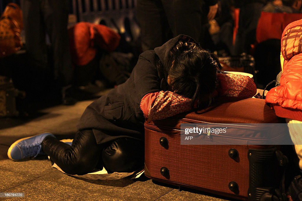 This picture taken on January 28, 2013 shows a woman sleeping on her luggage at Guangzhou train station, waiting for a train to go back home for the Lunar New Year, or Spring Festival. Passengers will log 220 million train rides during the 40-day travel season as they criss-cross the country to celebrate with their families, but just as making the trip home can be laborious -- often lasting one or two days -- so can simply acquiring a seat on the train, and every year complaints arise about the inefficiency or unfairness of the system, although an initiative allowing travelers to purchase tickets online aims to curb long queuing times. CHINA