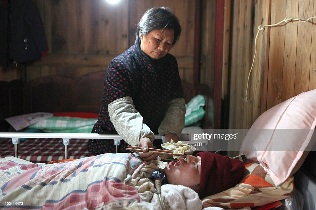 This picture taken on January 28, 2013 shows Fu Xuepeng, a former mechanic who was paralyzed in a road accident when he was 23 years old, breathing with the aide of a home-made ventilator (R) while his mother Wang Lanqin (L) feeds him at their home in Taizhou, east China's Zhejiang province. According to state media, a local hospital has decided to help Fu's parents after reports that they have kept their son alive for more than five years using a hand pumped PVC resuscitator bag and a ventilator made by a local DIY expert. They took turns compressing their son's bag 24-hours a day, seven days a week, until they had someone making them a medical ventilator with a motor, a speed controller, a pushing bar and an air bag, which cost 200 yuan (32 USD). But to minimize the electricity bill, which adds up to 5 to 6 yuan a day if the machine is left running all day, the couple still compresses the bag by hand during the day and turns on the machine only at night. CHINA OUT AFP PHOTO