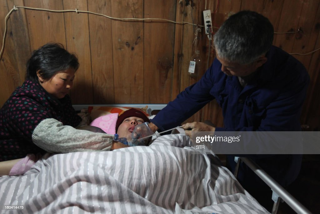 This picture taken on January 28, 2013 shows Fu Xuepeng (C), a former mechanic who was paralyzed in a This picture taken on January 28, 2013 shows Fu Xuepeng (R), a former mechanic who was paralyzed in a road accident when he was 23 years old, smiling on his bed as he breathes with a self-made ventilator while his mother Wang Lanqin watches, in their home in Taizhou, east China's Zhejiang province. According to state media, a local hospital has decided to help Fu's parents after reports that they have kept their son alive for more than five years using a hand pumped PVC resuscitator bag and a ventilator made by a local DIY expert. They took turns compressing their son's bag 24-hours a day, seven days a week, until they had someone making them a medical ventilator with a motor, a speed controller, a pushing bar and an air bag, which cost 200 yuan (32 USD). But to minimize the electricity bill, which adds up to 5 to 6 yuan a day if the machine is left running all day, the couple still compresses the bag by hand during the day and turns on the machine only at night. CHINA