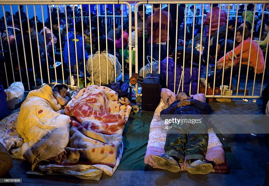 This picture taken on January 28, 2013 shows passengers sleeping on the square of Guangzhou train station to go home for the Spring Festival. Passengers will log 220 million train rides during the 40-day travel season as they criss-cross the country to celebrate with their families, but just as making the trip home can be laborious -- often lasting one or two days -- so can simply acquiring a seat on the train, and every year complaints arise about the inefficiency or unfairness of the system, although an initiative allowing travelers to purchase tickets online aims to curb long queuing times. CHINA OUT AFP PHOTO / BAI SHI