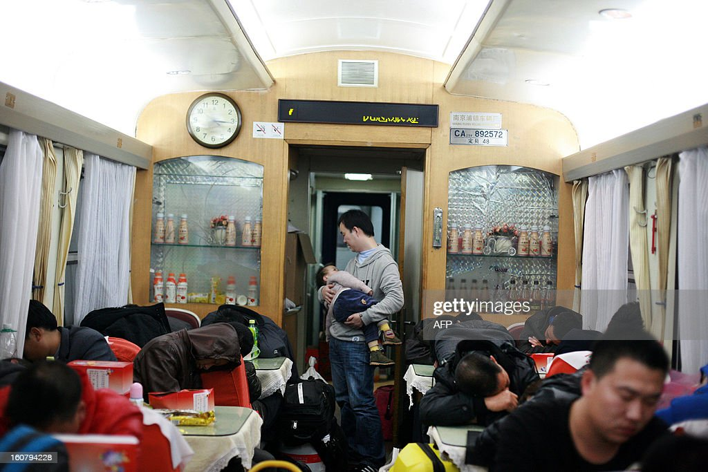 This picture taken on January 28, 2013 shows people sleeping in the dining car of a train from Guangzhou to Changchun as they head back to their hometowns for the Lunar New Year, or Spring Festival. Passengers will log 220 million train rides during the 40-day travel season as they criss-cross the country to celebrate with their families, but just as making the trip home can be laborious -- often lasting one or two days -- so can simply acquiring a seat on the train, and every year complaints arise about the inefficiency or unfairness of the system, although an initiative allowing travelers to purchase tickets online aims to curb long queuing times. CHINA