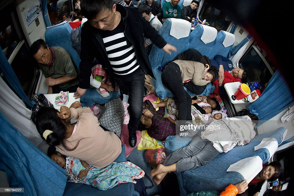 This picture taken on January 28, 2013 shows people sleeping wherever they can on a train from Guangzhou to Changchun as they head to their hometowns for the Lunar New Year, or Spring Festival. Passengers will log 220 million train rides during the 40-day travel season as they criss-cross the country to celebrate with their families, but just as making the trip home can be laborious -- often lasting one or two days -- so can simply acquiring a seat on the train, and every year complaints arise about the inefficiency or unfairness of the system, although an initiative allowing travelers to purchase tickets online aims to curb long queuing times. CHINA