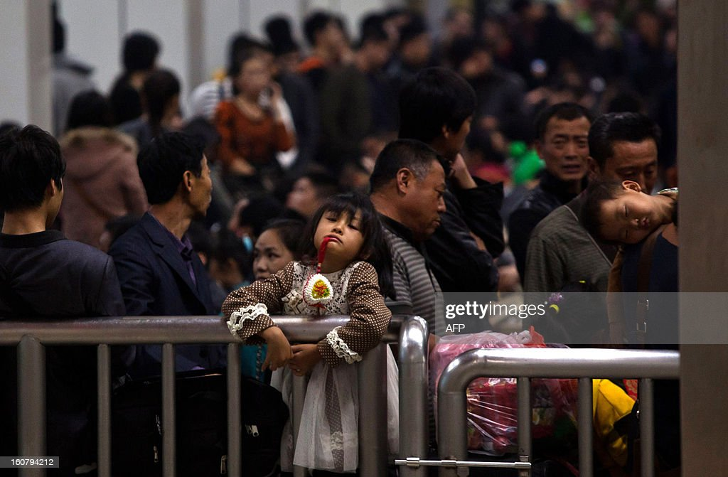 This picture taken on January 28, 2013 shows people waiting for their train to go back home at Guangzhou train station for Lunar New Year, or Spring Festival. Passengers will log 220 million train rides during the 40-day travel season as they criss-cross the country to celebrate with their families, but just as making the trip home can be laborious -- often lasting one or two days -- so can simply acquiring a seat on the train, and every year complaints arise about the inefficiency or unfairness of the system, although an initiative allowing travelers to purchase tickets online aims to curb long queuing times. CHINA