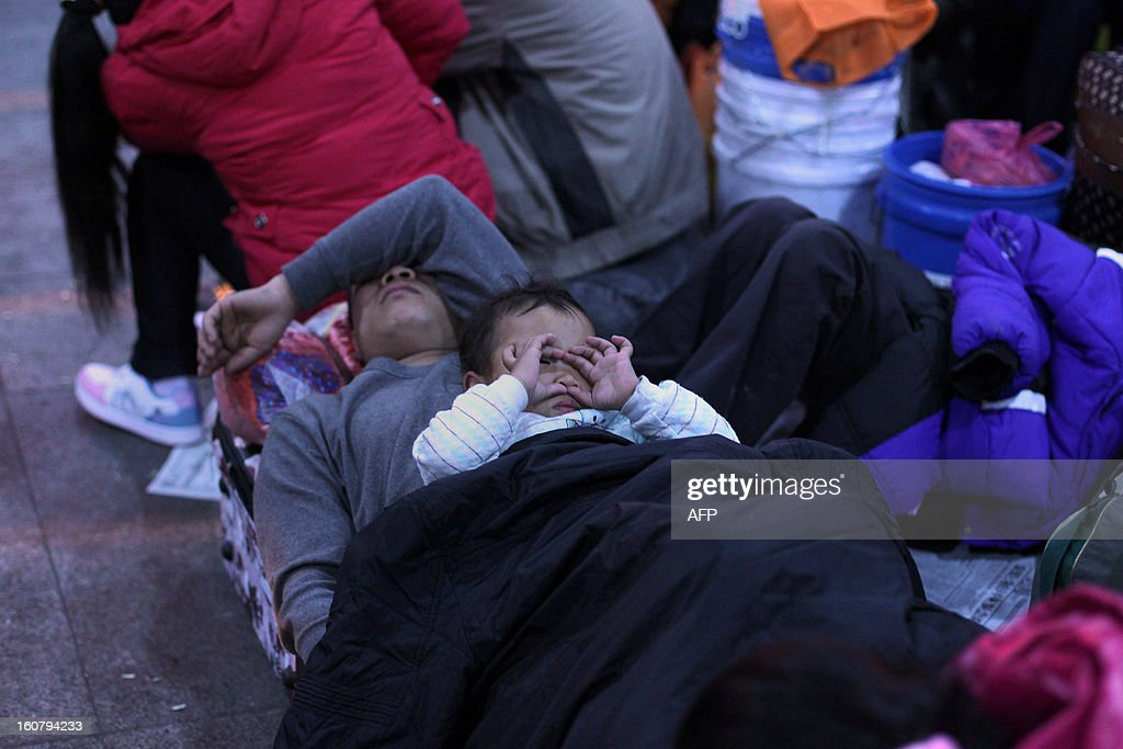 This picture taken on January 28, 2013 shows two-year-old Xingxing lying on his father in the square of Guangzhou train station waiting for their train back home for Lunar New Year holidays or Spring Festival. Passengers will log 220 million train rides during the 40-day travel season as they criss-cross the country to celebrate with their families, but just as making the trip home can be laborious -- often lasting one or two days -- so can simply acquiring a seat on the train, and every year complaints arise about the inefficiency or unfairness of the system, although an initiative allowing travelers to purchase tickets online aims to curb long queuing times. CHINA