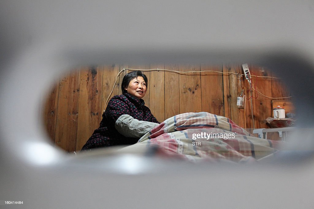 This picture taken on January 28, 2013 shows Wang Lanqin (L) attending to her son Fu Xuepeng (not pictured), a former mechanic who was paralyzed in a road accident when he was 23 years old, in their home in Taizhou, east China's Zhejiang province. According to state media, a local hospital has decided to help Fu's parents after reports that they have kept their son alive for more than five years using a hand pumped PVC resuscitator bag and a ventilator made by a local DIY expert. They took turns compressing their son's bag 24-hours a day, seven days a week, until they had someone making them a medical ventilator with a motor, a speed controller, a pushing bar and an air bag, which cost 200 yuan (32 USD). But to minimize the electricity bill, which adds up to 5 to 6 yuan a day if the machine is left running all day, the couple still compresses the bag by hand during the day and turns on the machine only at night. CHINA OUT AFP PHOTO