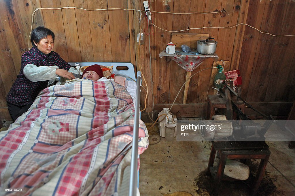 This picture taken on January 28, 2013 shows Wang Lanqin (L) compressing a PVC resuscitator pump to help her son Fu Xuepeng, a former mechanic who was paralyzed in a road accident when he was 23 years old, to breathe and live on in their home in Taizhou, east China's Zhejiang province. According to state media, a local hospital has decided to help Fu's parents after reports that they have kept their son alive for more than five years using a hand pumped PVC resuscitator bag and a ventilator made by a local DIY expert. They took turns compressing their son's bag 24-hours a day, seven days a week, until they had someone making them a medical ventilator with a motor, a speed controller, a pushing bar and an air bag, which cost 200 yuan (32 USD). But to minimize the electricity bill, which adds up to 5 to 6 yuan a day if the machine is left running all day, the couple still compresses the bag by hand during the day and turns on the machine only at night. CHINA OUT AFP PHOTO