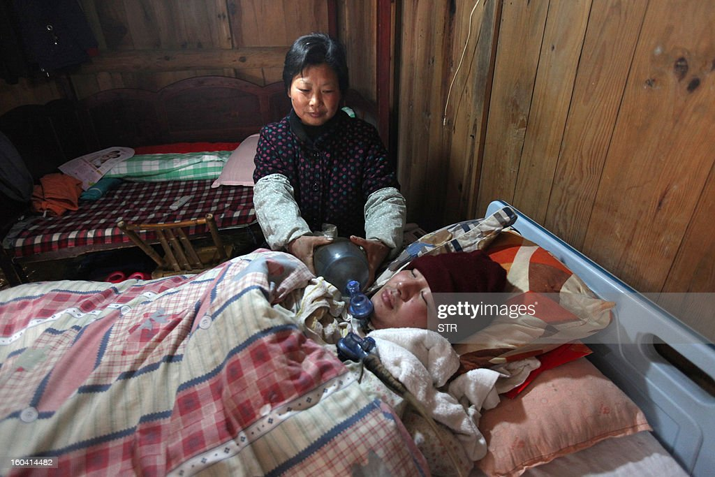 This picture taken on January 28, 2013 shows Wang Lanqin (back) compressing a PVC resuscitator pump to help her son Fu Xuepeng, a former mechanic who was paralyzed in a road accident when he was 23 years old, to breathe and live on in their home in Taizhou, east China's Zhejiang province. According to state media, a local hospital has decided to help Fu's parents after reports that they have kept their son alive for more than five years using a hand pumped PVC resuscitator bag and a ventilator made by a local DIY expert. They took turns compressing their son's bag 24-hours a day, seven days a week, until they had someone making them a medical ventilator with a motor, a speed controller, a pushing bar and an air bag, which cost 200 yuan (32 USD). But to minimize the electricity bill, which adds up to 5 to 6 yuan a day if the machine is left running all day, the couple still compresses the bag by hand during the day and turns on the machine only at night. CHINA