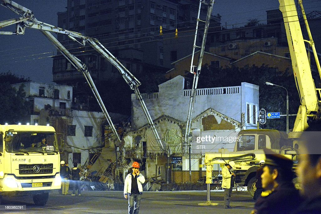 This picture taken on January 28, 2013 shows workers using machinery to fill in a sinkhole that buildings collapsed into near a subway construction site in Guangzhou, south China's Guangdong province. The hole measured about 1,000 square feet across and was around 30 feet deep, but no one was killed, according to a state media report. CHINA OUT AFP PHOTO