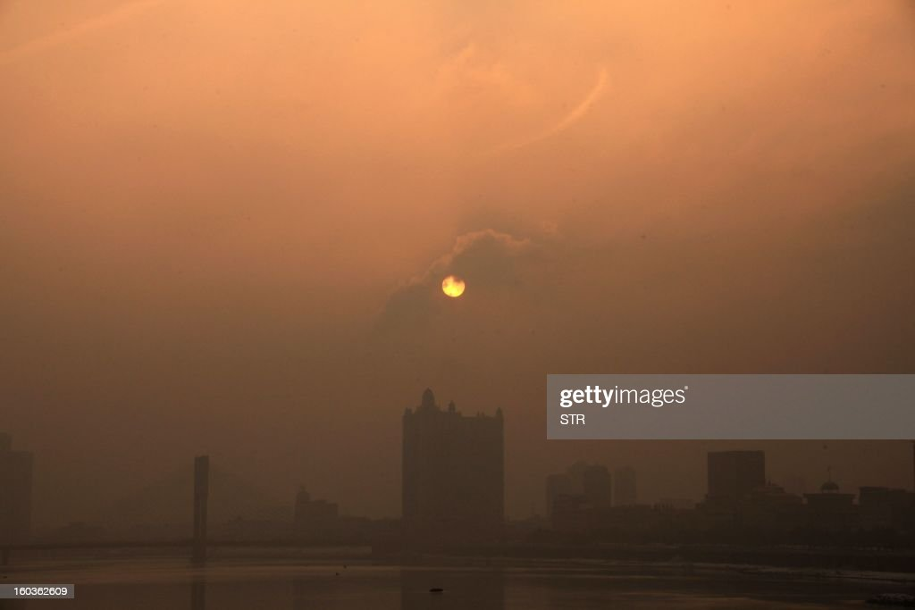 This picture taken on January 29, 2013 shows a general view of buildings in the heavy smog in Jilin, northeast China's Jilin province. Beijing urged residents to stay indoors on January 30 as emergency measures were rolled out aimed at countering a heavy cloud of smog blanketing the Chinese capital and swathes of the country. CHINA