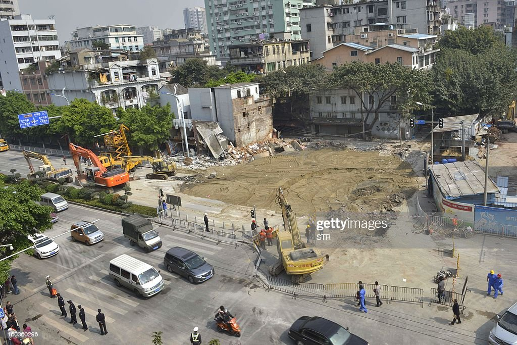 This picture taken on January 29, 2013 shows rescuers filling the sinkhole that buildings collapsed into the night before near a subway construction site in Guangzhou, south China's Guangdong province. The hole measured about 1,000 square feet across and was around 30 feet deep, but no one was killed, according to a state media report. CHINA